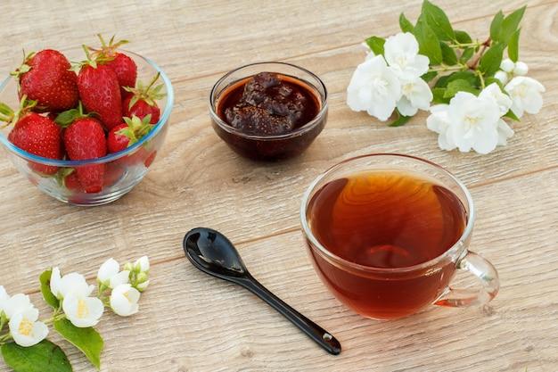 Szklana filiżanka herbaty, domowej roboty dżem truskawkowy i świeże truskawki w miskach, łyżka i białe kwiaty jaśminu na drewnianych deskach. widok z góry.