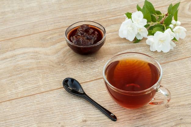Szklana filiżanka herbaty, domowej roboty dżem truskawkowy, łyżka i białe kwiaty jaśminu na drewniane tła. widok z góry.