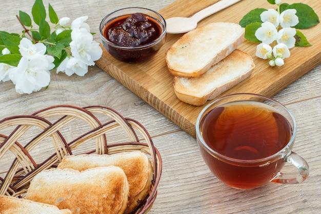 Szklana filiżanka herbaty, domowy dżem truskawkowy, chleb na drewnianej desce do krojenia, świeże truskawki, łyżka, grzanki w wiklinowym koszu i białe kwiaty jaśminu na drewnianym tle. widok z góry.