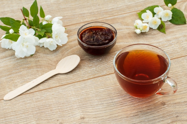 Szklana filiżanka herbaty, domowy dżem truskawkowy, drewniana łyżka i białe kwiaty jaśminu na drewnianym tle. widok z góry.