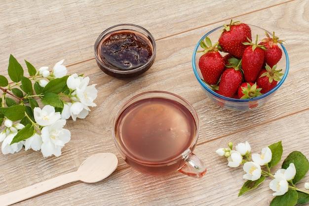 Szklana filiżanka herbaty, domowy dżem truskawkowy i świeże truskawki w miskach, drewniana łyżka i białe kwiaty jaśminu na drewnianym tle. widok z góry.