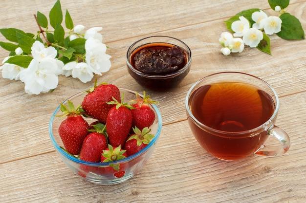 Szklana filiżanka herbaty, domowy dżem truskawkowy i świeże truskawki w miskach i białe kwiaty jaśminu na drewnianym tle. widok z góry.