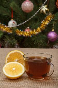 Szklana filiżanka herbaty i kawałki cytryny na stole z worem i choinką jodłą z zabawkami kulkami i girlandami w tle.