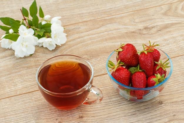Szklana filiżanka herbaty, miska ze świeżymi truskawkami i białymi kwiatami jaśminu na drewnianym tle. widok z góry.
