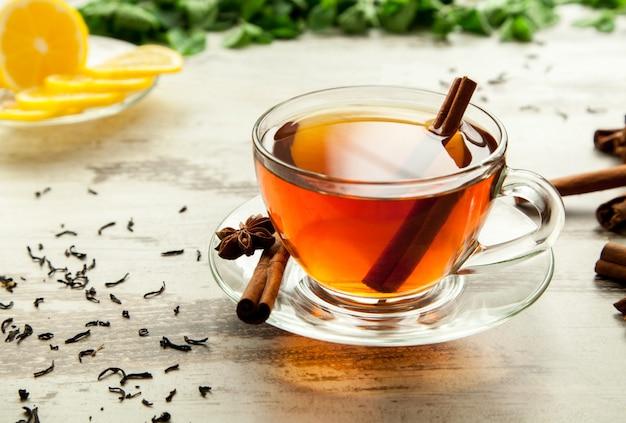 Szklana filiżanka herbaty na drewnianym stole z plasterkami cytryny i cynamonu.