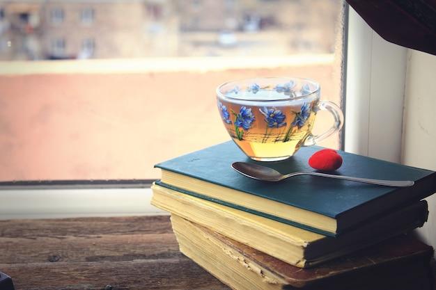 Szklana filiżanka herbaty na książkach na oknie