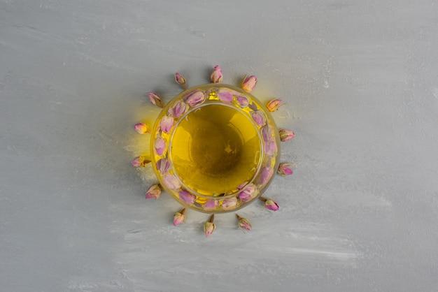 Szklana filiżanka herbaty na szarym stole.