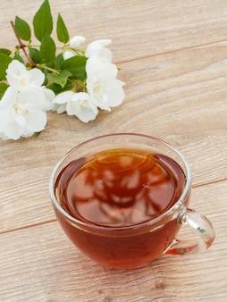 Szklana filiżanka herbaty z białymi kwiatami jaśminu na drewniane tła. widok z góry.