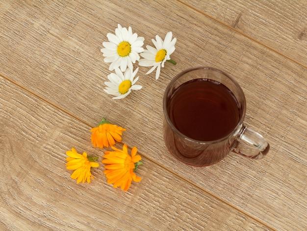 Szklana filiżanka herbaty z białymi kwiatami rumianku i żółtymi kwiatami nagietka na drewnianym pulpicie. widok z góry.
