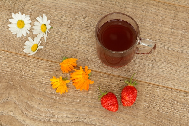 Szklana filiżanka herbaty z białymi kwiatami rumianku, żółtymi kwiatami nagietka i truskawkami na drewnianym pulpicie. widok z góry.