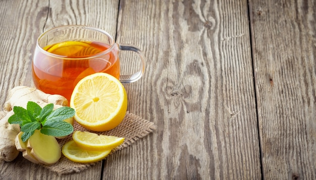 Szklana filiżanka herbaty z cytryną, miętą i imbirem na drewnianym stole w stylu rustykalnym.