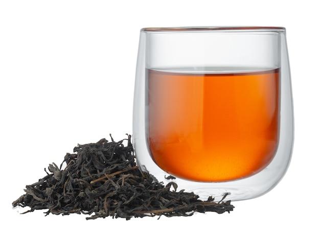 Szklana filiżanka herbaty z suchymi liśćmi herbaty na białym tle