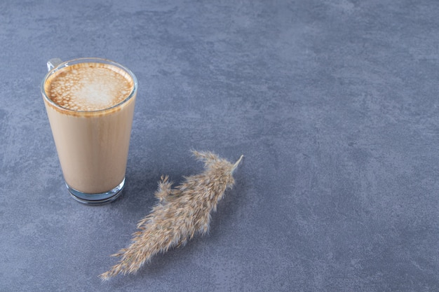 Szklana filiżanka kawy latte obok trawy pampasowej, na niebieskim stole.