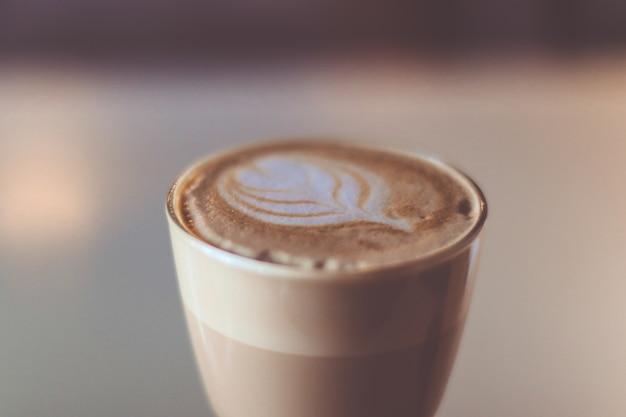 Szklana filiżanka kawy na stole w kawiarni. gorący latte z rozmycia tła