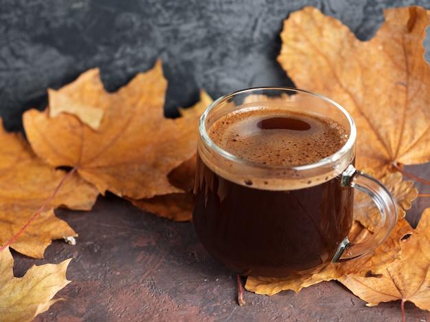 Szklana filiżanka kawy w jesień liściach. komfort w domu rano
