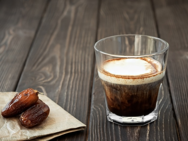 Szklana filiżanka kawy z mlekiem na ciemnej drewnianej powierzchni
