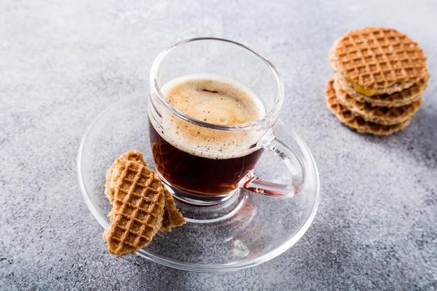 Szklana filiżanka kawy z syropowatymi ciastkami