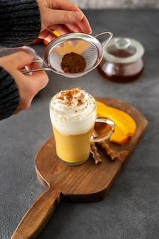 Szklana filiżanka pikantnego cappuccino z dyni na szarej powierzchni