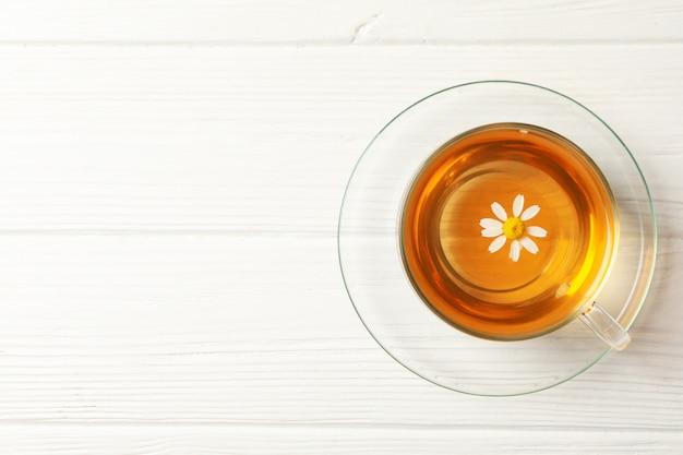 Szklana filiżanka rumianek herbata na drewnie, odgórny widok