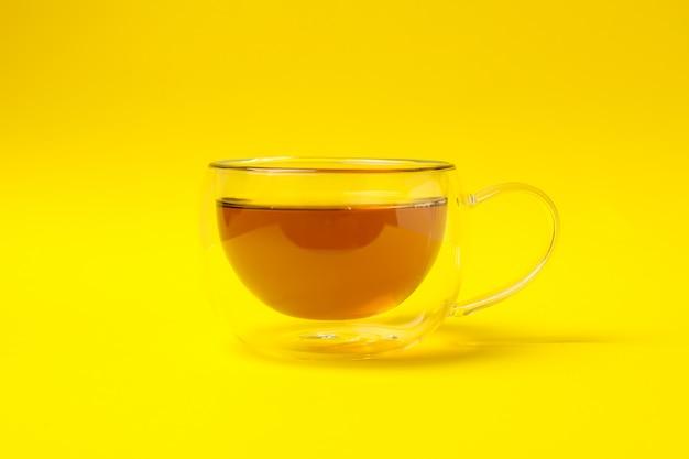 Szklana filiżanka rumianku herbata na kolorze żółtym