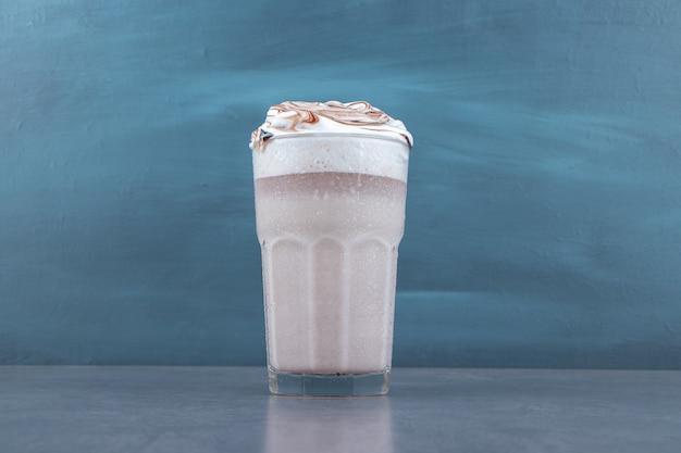 Szklana filiżanka słodkiego koktajlu mlecznego z bitą śmietaną
