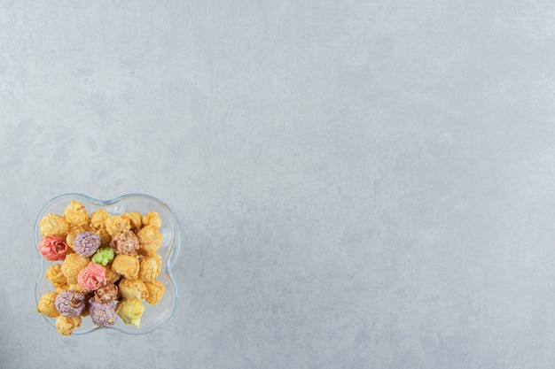 Szklana filiżanka słodkiego wielokolorowego popcornu.
