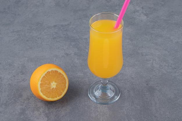 Szklana filiżanka świeżego soku pomarańczowego z plasterkiem pomarańczy i słomką