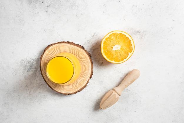 Szklana filiżanka świeżego soku z plasterkiem pomarańczy.