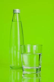 Szklana filiżanka wody mineralnej na zieleni