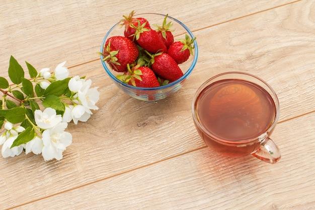 Szklana filiżanka zielonej herbaty, miska ze świeżymi truskawkami i białymi kwiatami jaśminu na drewnianym tle. widok z góry.