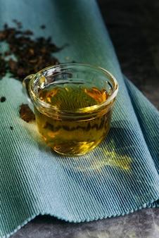 Szklana herbata ziołowa na niebieskiej serwetce
