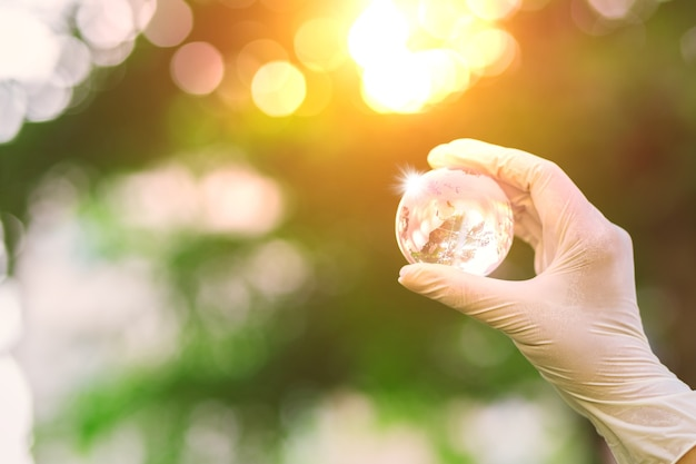 Szklana kula pod ręką ze wschodem słońca nad brzegiem rzeki