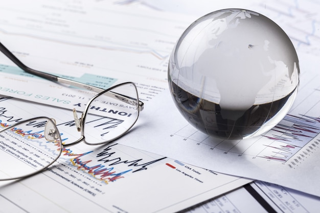 Szklana kula ziemska w promieniach światła na tle wykresów biznesowych