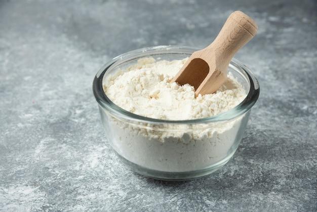 Szklana miska mąki na marmurze.