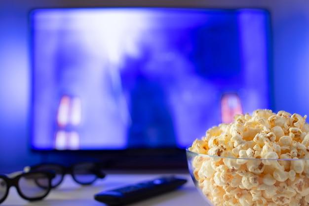 Szklana miska popcornu i pilota.