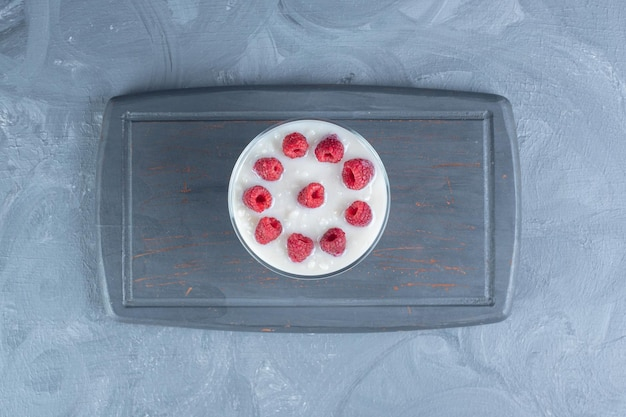 Szklana miska ryżu mlecznego z malinami na granatowym talerzu na marmurowym tle.