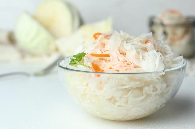 Szklana miska smacznej kiszonej kapusty na białym stole zbliżenie
