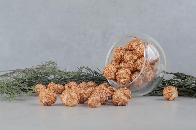 Szklana miska spadła na gałąź, rozlewając na marmurowy stół popcorn pokryty cukierkami.