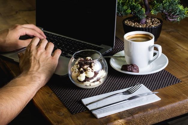 Szklana miska tiramisu i filiżanka espresso służyły człowiekowi pracującemu w zeszycie
