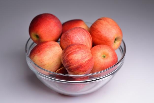 Szklana miska wypełniona czerwonymi jabłkami na szarym tle