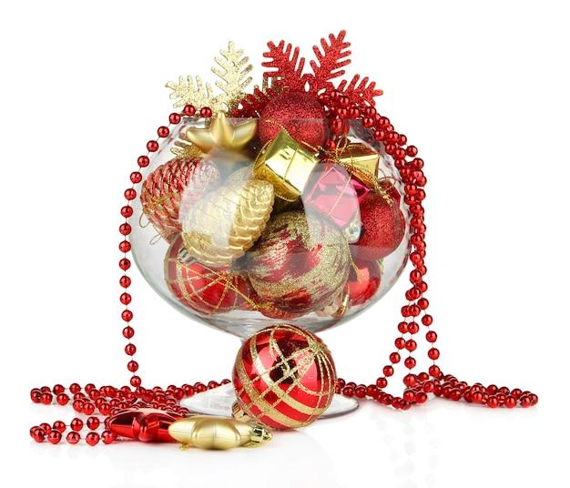 Szklana miska wypełniona dekoracjami świątecznymi, na białym tle