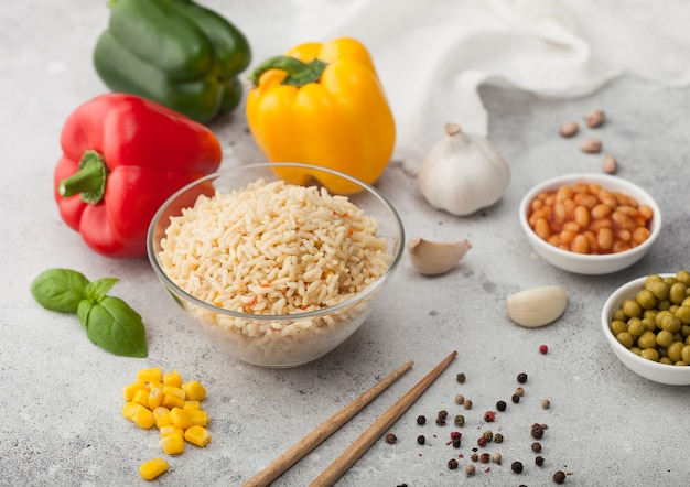 Szklana miska z gotowanym ryżem basmati długoziarnistym z warzywami na jasnym tle z patyczkami i papryką paprykową z kukurydzą, fasolą i groszkiem.