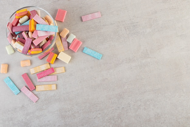 Szklana miska z kamiennym stołem z kolorowymi gumami do żucia.