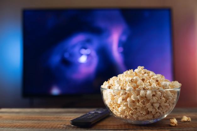 Szklana miska z popcornem i działającym telewizorem.