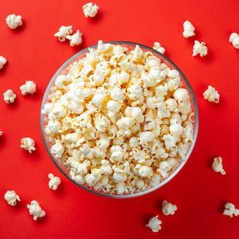 Szklana miska z solonym popcornem.
