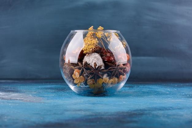 Szklana miska z suszonymi kwiatami i owocami na niebieskim stole.