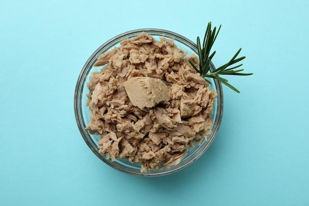 Szklana miska z tuńczykiem w puszkach na niebieskim tle