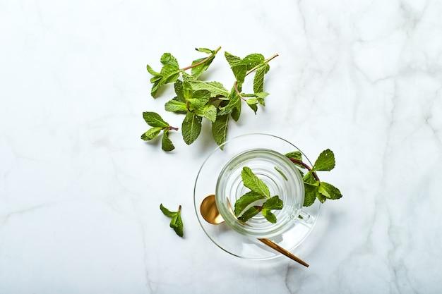 Szklana pusta filiżanka herbaty i zielone liście mięty na marmurowym stole