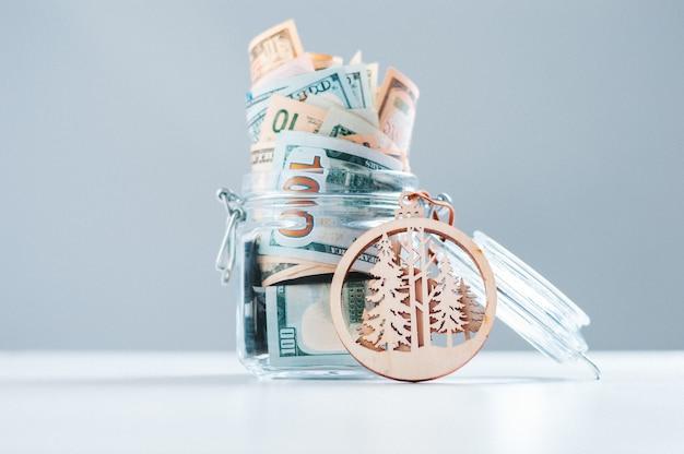 Szklana skarbonka pełna pieniędzy. pojęcie ochrony lasu, planety i przyrody
