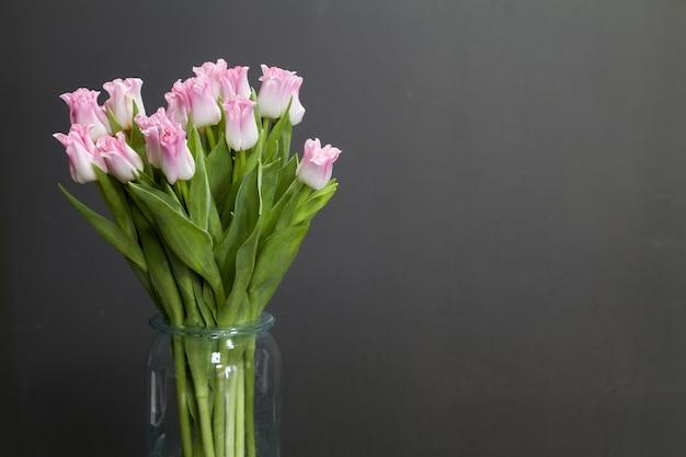 Szklana waza z różowymi tulipanami na ciemnym drewnianym stole, powitania tle lub pojęciu